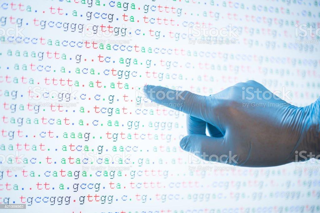 Código de ADN en pantalla con una mano toque la pantalla - foto de stock