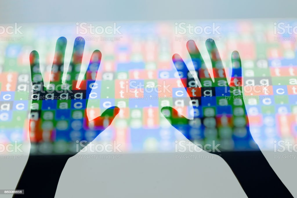 DNA code on screen with two hands touch the screen stock photo