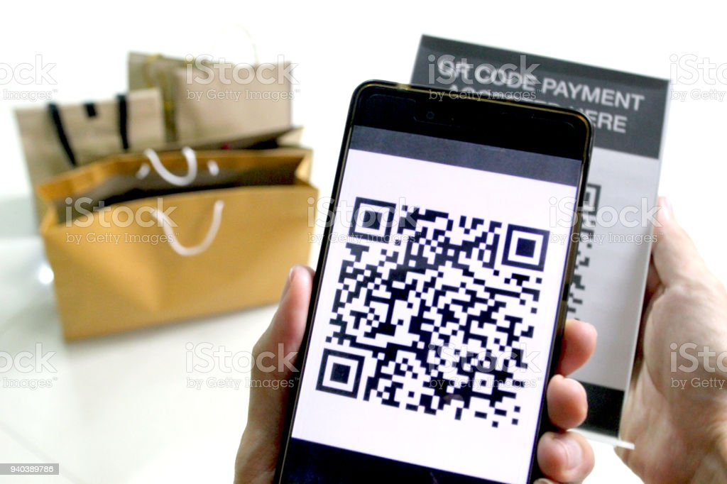 QR code payment for shopping, hand holding mobile phone to scan the sign of qr code and grant money to another account stock photo