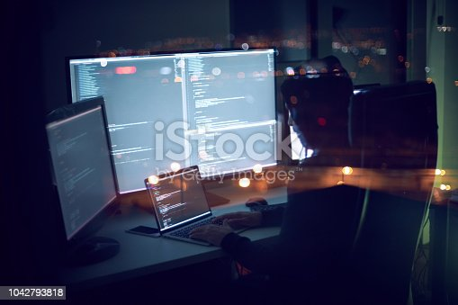 Computer programmer writing code in front of the monitors at late night.