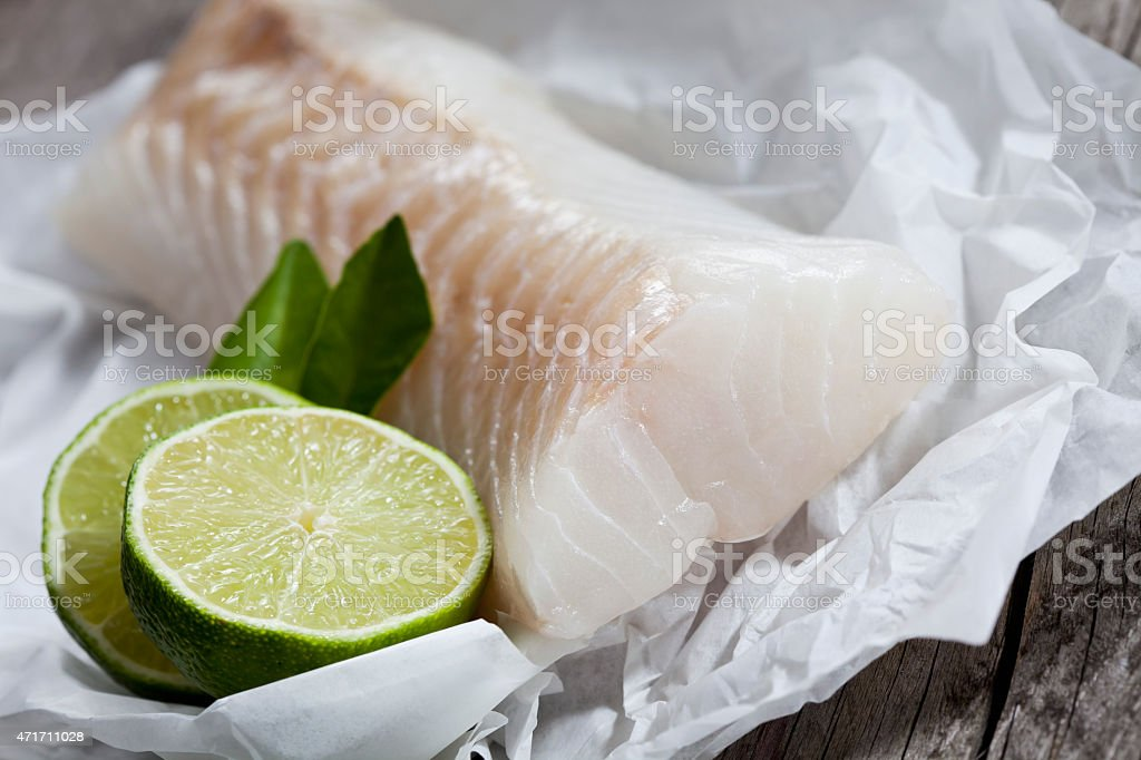 Codfish, fillet and lime on greaseproof paper stock photo