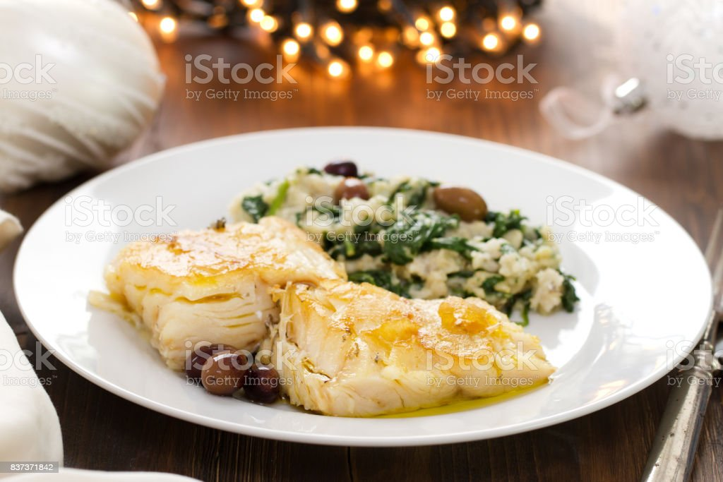 codfish with bread and spinach on white plate on brown wooden background stock photo