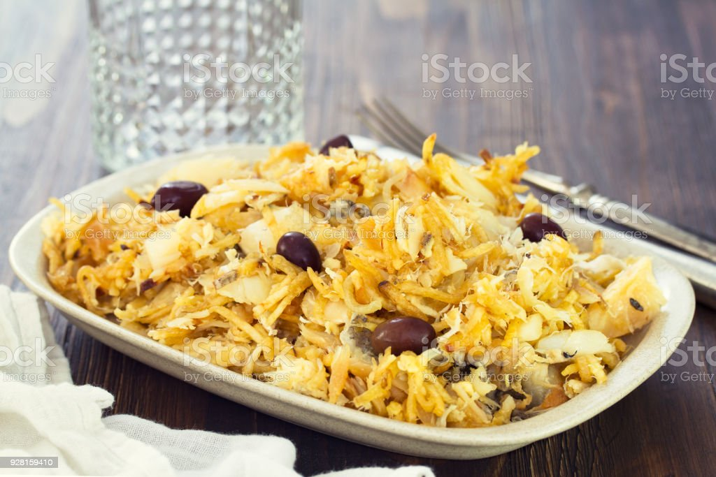 codfish with potato chips and olives on white plate stock photo