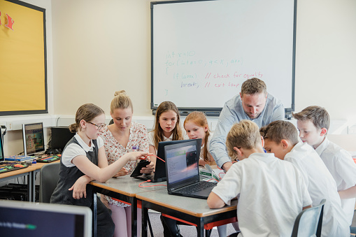Students in a high school classroom are learning computer coding and circuits on laptops with two teachers.