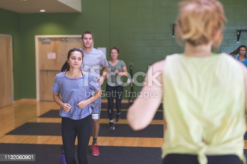 A female instructor leads a co-ed workout class at a modern fitness center. The shot is over her shoulder and focused on a brunette college-age female in the front.