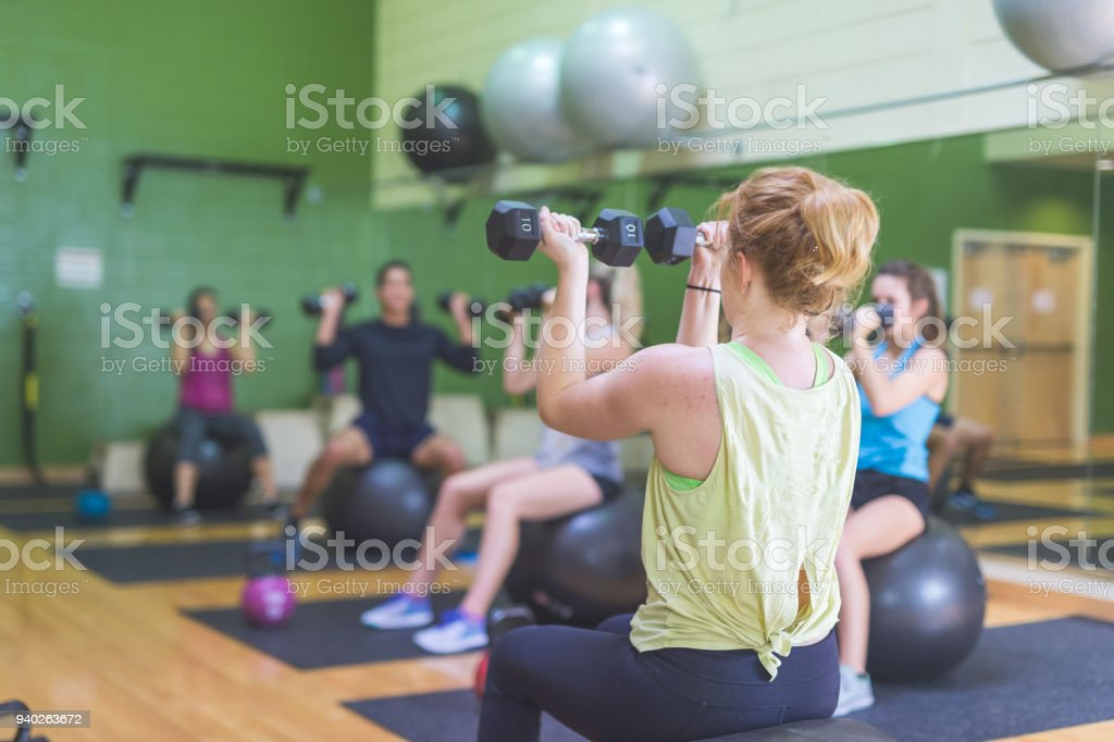 Co-ed group of college-age students exercise together at a modern fitness facility stock photo