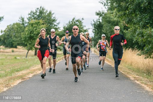 A mixed group of senior triathletes train for the running leg together. They're on a paved trail adjacent to a forested field area. The focus is on a senior woman second from the front.