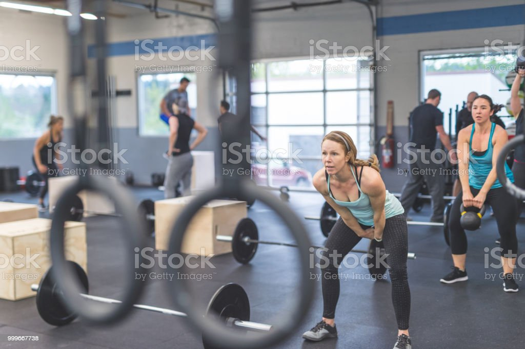 A group of women work out together in a modern gym. Several women are...