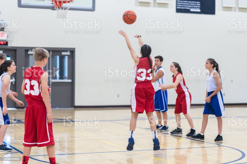 A female player shoots a free throw during a high school co-ed...