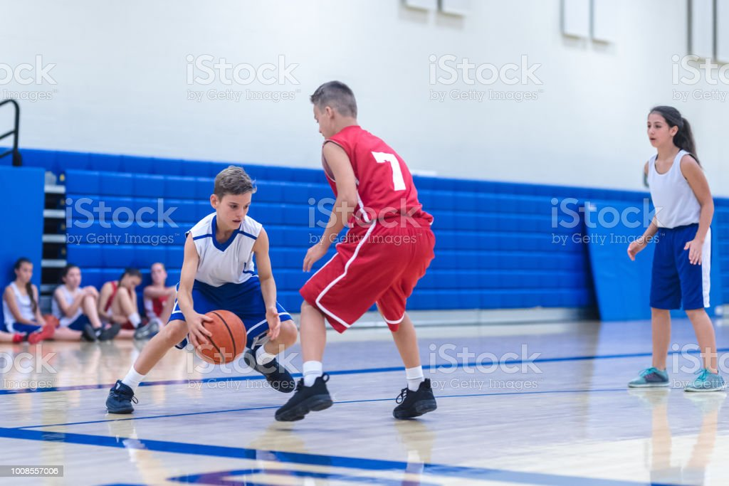 A male player tries to dribble around a defender during a co-ed high...