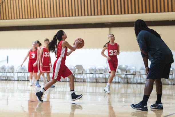 Co-ed high school basketball practice Coach has his co-ed basketball team run layup drills during practice. One girl is dribbling and about to pass to her teammate. basketball sport stock pictures, royalty-free photos & images