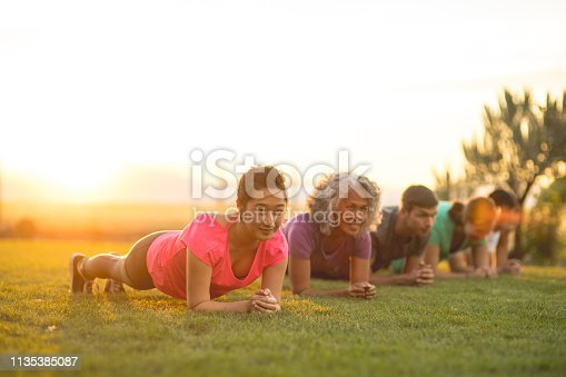 A group of adults attending a fitness class outdoors are doing leg stretches. The participants are arranged in a line. The focus is on a young ethnic woman who is smiling as she stretches and smiles.