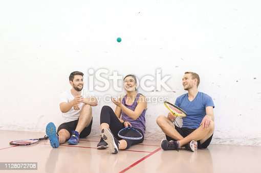 Two college-age men and a woman take a break from playing racquetball. They are sitting up against the court wall and talking before playing again.