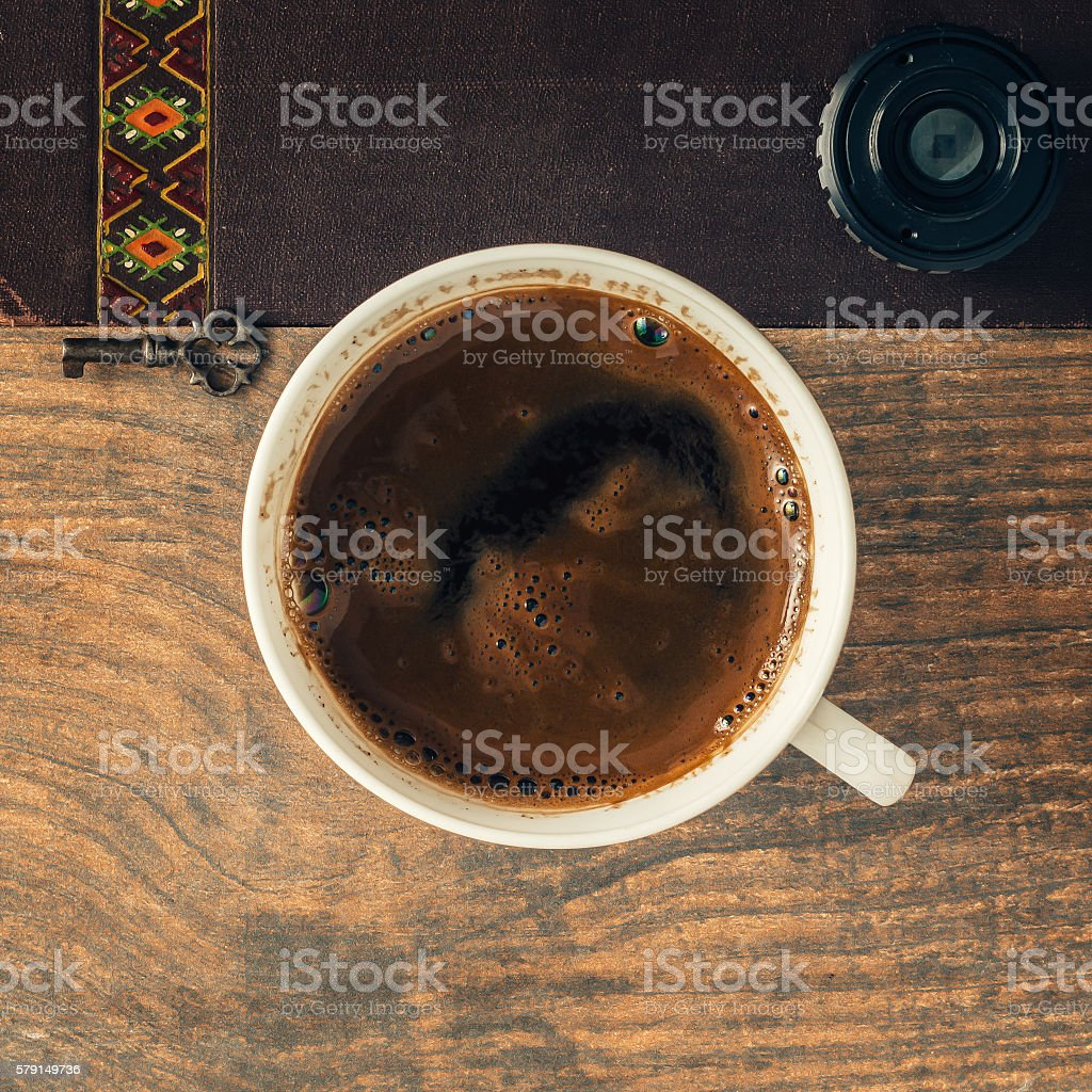 Cofee cup on wooden background with leather and old key. stock photo