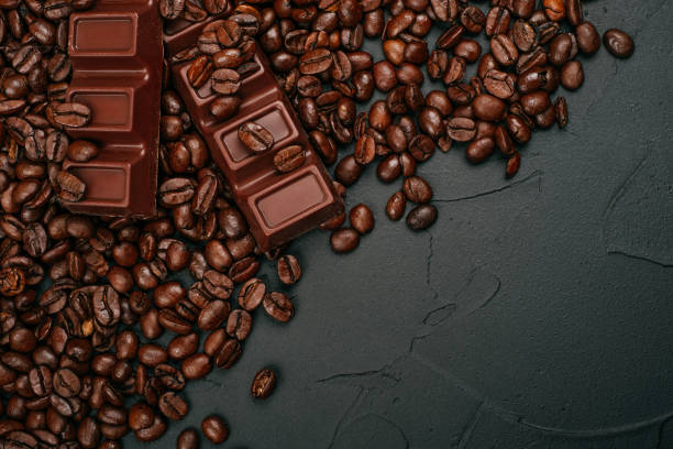Coffe and chocolate Roasted coffee beans and two bars of milk chocolate on the black concrete stone background. Flatlay style. caffeine stock pictures, royalty-free photos & images