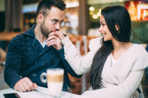 Coffe break Young couple at cafe drinking coffee. Man kissing girl's hand kissinghand stock pictures, royalty-free photos & images