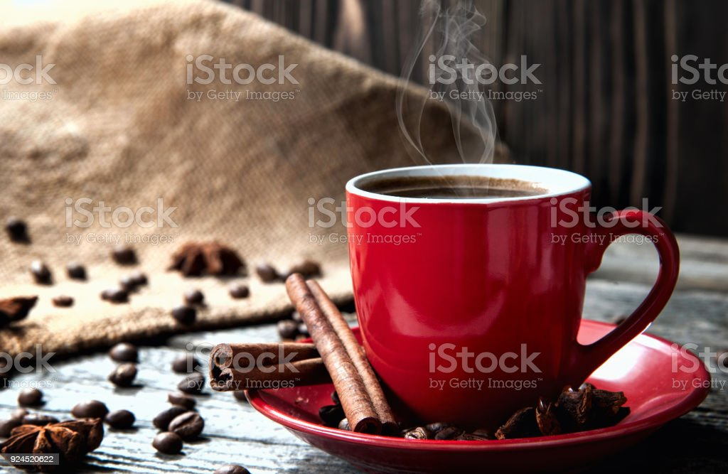 Kaffee in roten Becher auf Holztisch mit Kaffeebohnen und Zimt – Foto