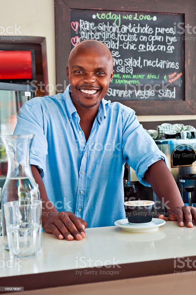 Coffe Shop Owner Friendly african man standing behind the bar counter and serving coffee in coffee shop, smiling at camera. Adult Stock Photo