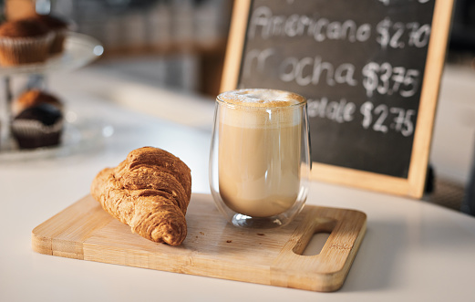 Closeup shot of a croissant and a cup of coffee on a wooden serving board in a cafe