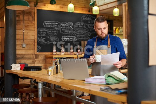 a coffee shop owner checks the delivery notes in his bookkeeping folder on the counter of his busy coffee shop and cross checks them with his online accountancy via his laptop at the end of a busy day .
