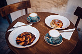 European breakfast with latte coffee and rolls served on cafe wooden table in the morning