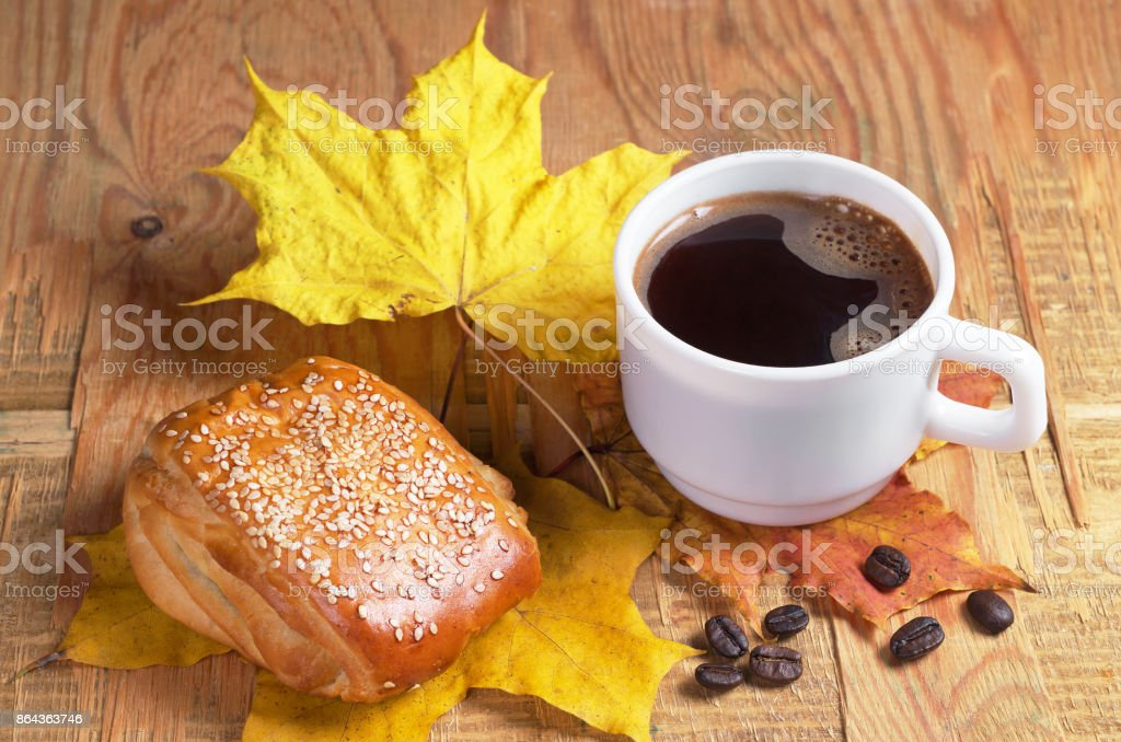 Cup of hot coffee, sweet bun with jam and flax seeds on old wooden...