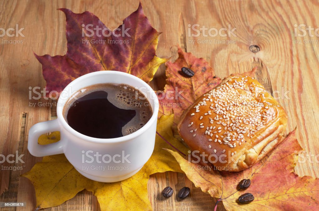 Cup of hot coffee, a sweet bun with jam and sesame on an old wooden...