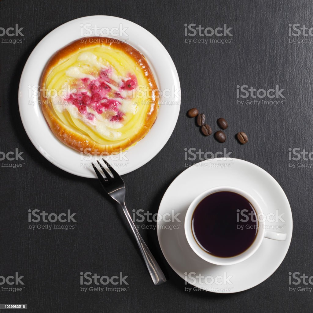 Cup of coffee and bun with custard and berries on black stone...