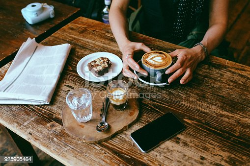 Vintage low key image of a coffee on the table in a cafe in East London. Young woman is having a cappuccino and some sweets, a delicious chocolate cake.
