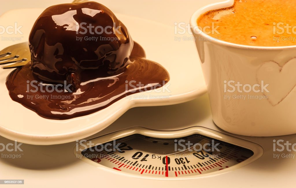 Coffee and chocolate cake on weighing scale. zbiór zdjęć royalty-free