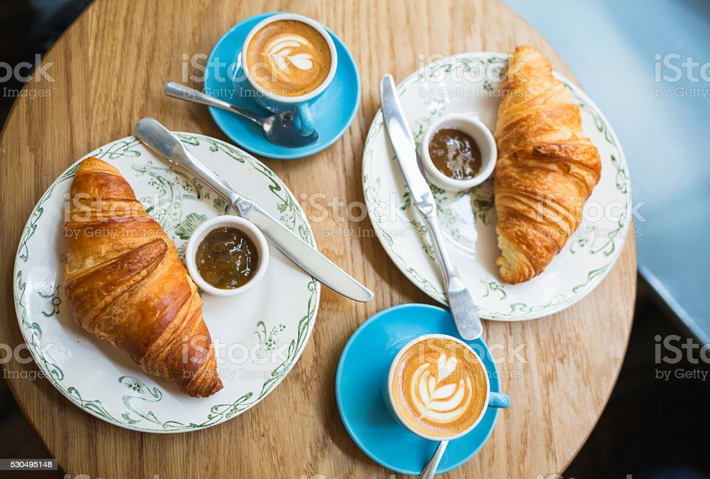 Coffee and croissant. French style breakfast in cafe (Paris, France) stock photo