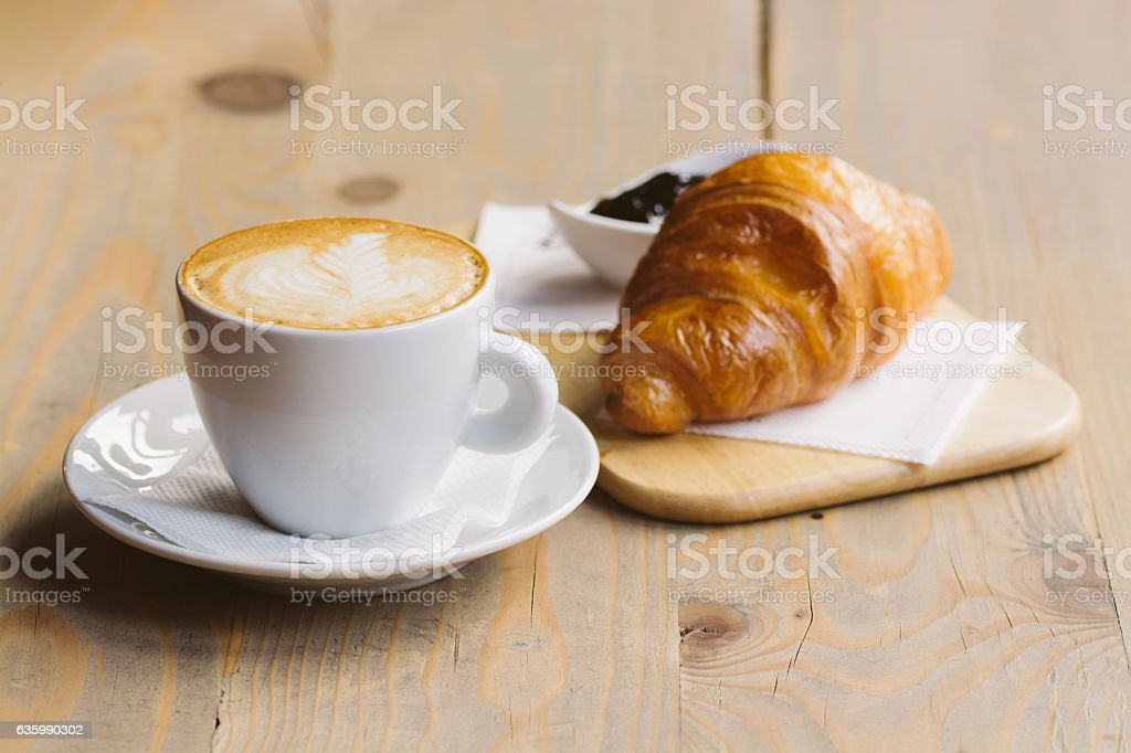 Coffee and Croissant on a wooden table stock photo