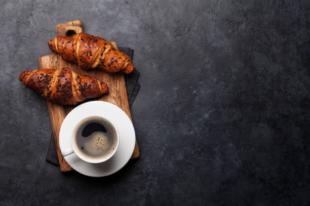 Coffee and croissant Coffee and croissant on stone table. French breakfast. Top view flat lay with copy space for your text croissant stock pictures, royalty-free photos & images