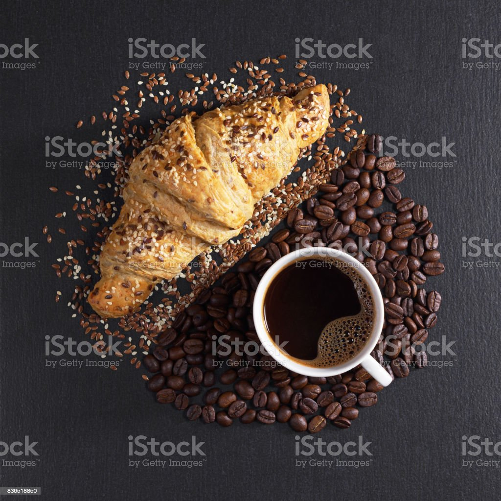 Cup of hot coffee and tasty croissant with sesame seeds on black...