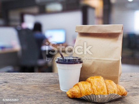 istock coffee and croissant with paper bag on wooden table 526553052