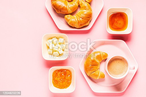 Coffee and croissants for breakfast on a pink background, top view, flat lay.
