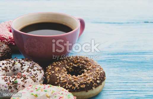 Coffee and donut on wooden blue background