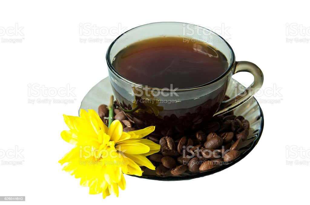 Cup poured coffee into a saucer of coffee beans and the yellow flower