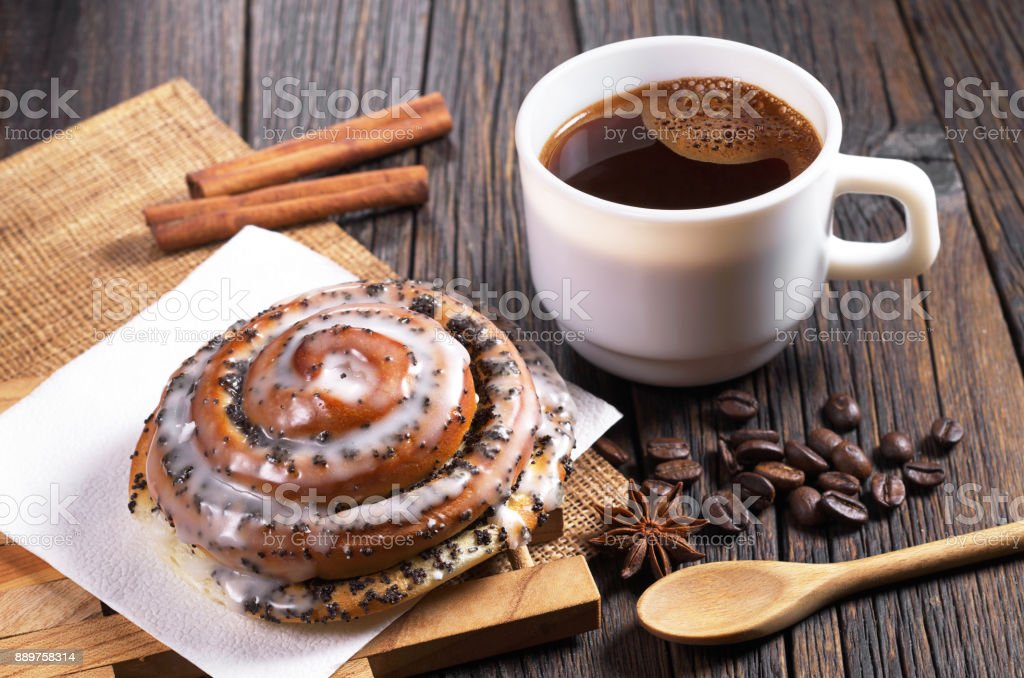 Cup of coffee and fresh bun with poppy seeds and sugar icing on old...