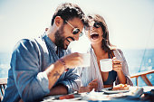 Young couple laughing and drinking coffee at the sidewalk cafe on the beach.