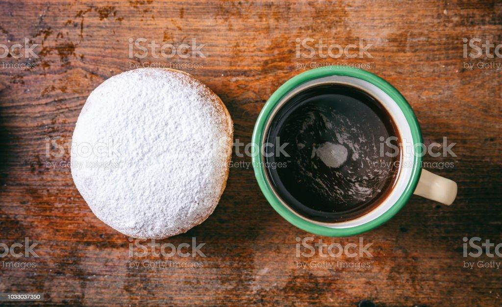 Kaffee und Krapfen mit Puderzucker, zwei, top Aussicht und isoliert, hölzernen Hintergrund. – Foto