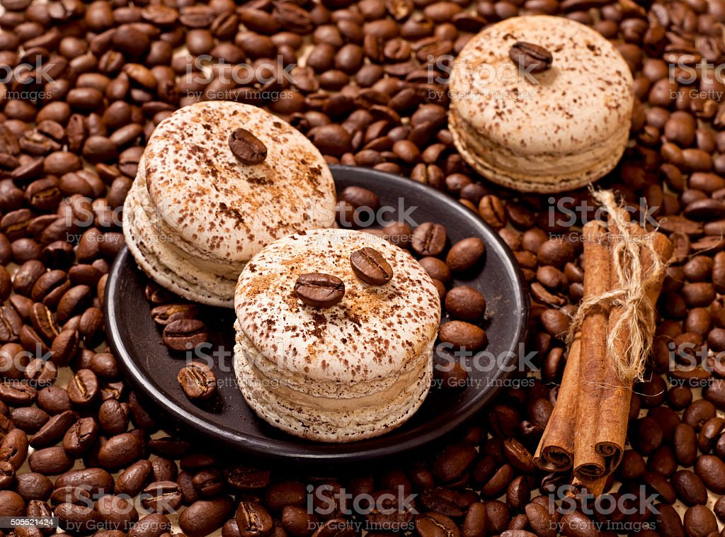 coffee and macaroons macaroons and cinnamon on coffee beans background Baked Stock Photo