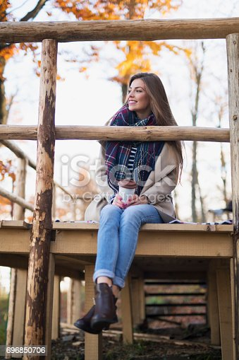 Beautiful young woman sitting on the wooden platform, drinking coffee and enjoying the beautiful autumn environment.