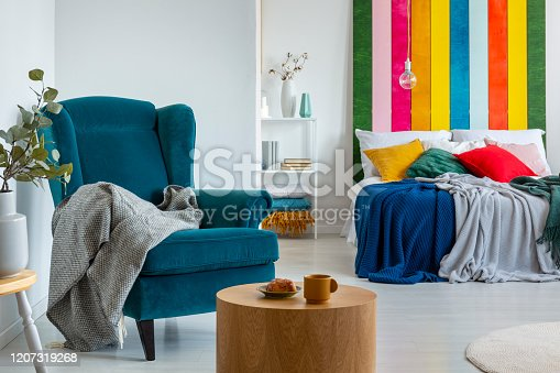 Coffee and peace of cake next to wing back chair with grey blanket in warm bedroom interior