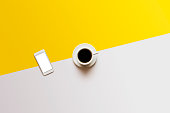 Coffee and phone on white yellow color block background
