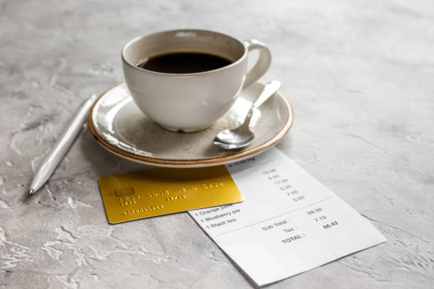 coffee and receipt bill for payment by credit card on stone table background stock photo