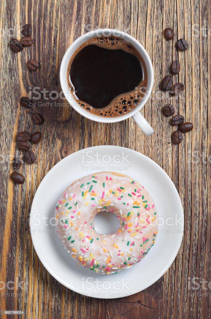 Cup of coffee and sweet donut with frosting and colorful sprinkles in...