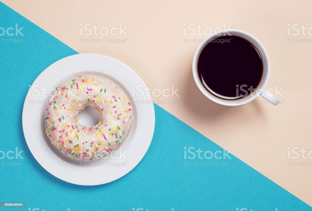 Cup of coffee and tasty donut with glaze and colorful sprinkles is...