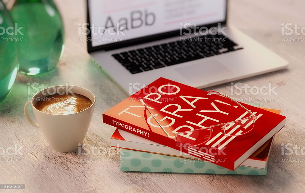 coffee and typography books with out of focused computer stock photo