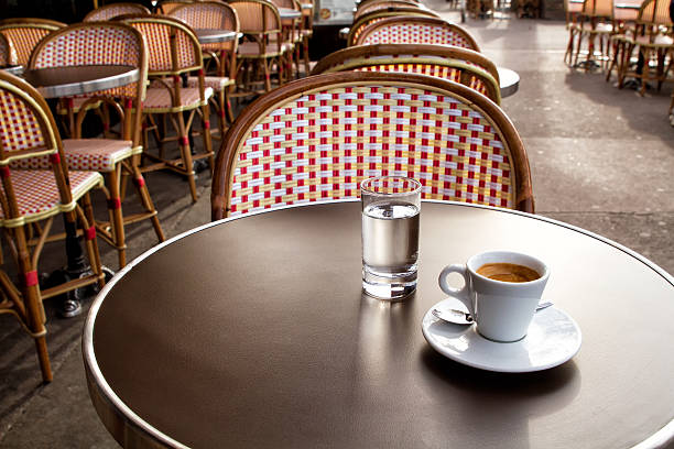 Coffee and water on a table of parisian's bar stock photo